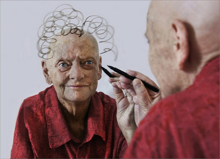 portrait of an old lady with cancer drawing hair on her reflection in the mirror