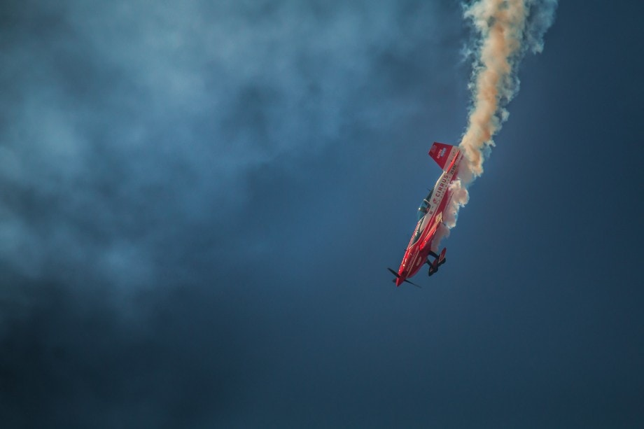 photo of an airplane doing tricks at an airshow